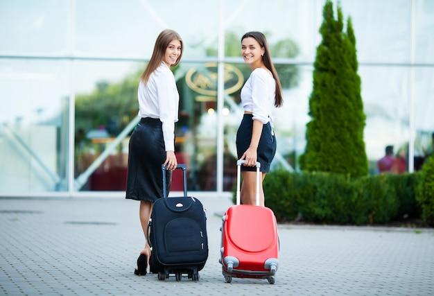 Dwie szczęśliwe dziewczyny podróżujące razem za granicę, niosące bagaż walizki na lotnisku