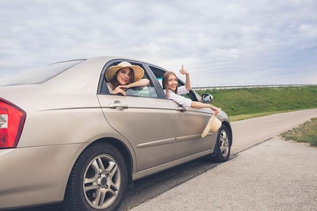 Dwie szczęśliwe dziewczyny podróżujące w samochodzie
