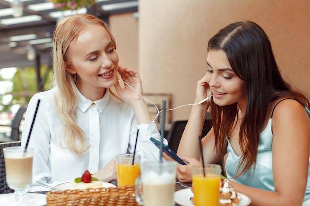 Dwie szczęśliwe dziewczyny razem słuchają muzyki w słuchawkach w miłej kawiarni. ciesz się muzyką i rozrywką