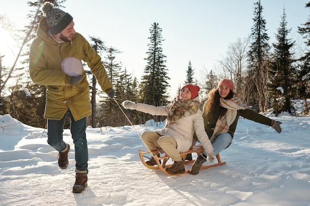 Dwie szczęśliwe dziewczyny śmiejące się, podczas gdy młody mężczyzna ciągnie sanie