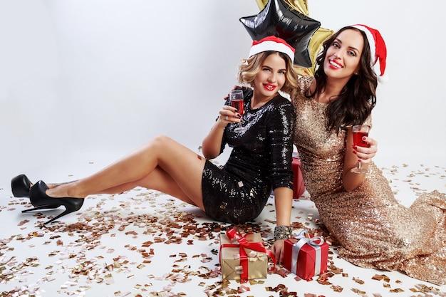 Dwie szczęśliwe dziewczyny w czerwonym świątecznym czapce świętego mikołaja siedzi na podłodze, pije wino, śmieje się, ciesząc się razem. ubrana w błyszczącą czarno-złotą suknię wieczorową.