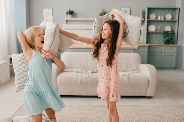 Dwie szczęśliwe dziewczyny w pięknych sukienkach siedzące na huśtawce z pudełkami w dłoniach w pokoju dziecięcym