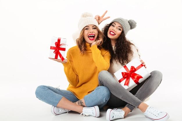 Dwie szczęśliwe dziewczyny w swetrach i czapkach, siedzące razem z prezentami na podłodze podczas zabawy nad białą ścianą