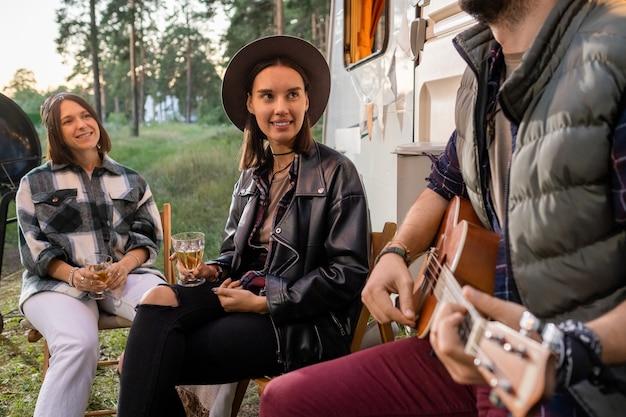 Dwie szczęśliwe dziewczyny z napojami słuchające młodego mężczyzny grającego na gitarze