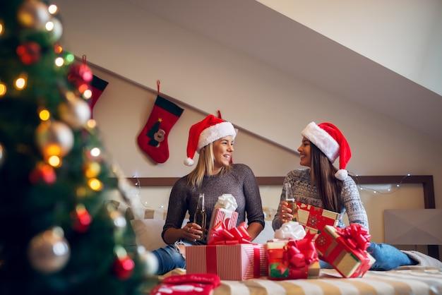 Dwie szczęśliwe dziewczyny z santa hat siedzi na łóżku na święta bożego narodzenia i pije niedźwiedź zadowolony