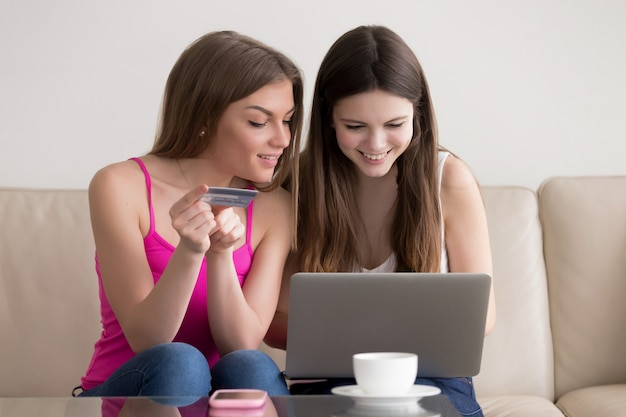Dwie szczęśliwe dziewczyny zamawiające towary w internecie
