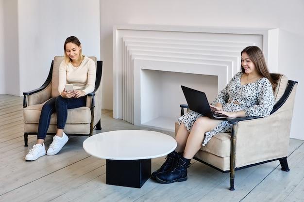 Dwie szczęśliwe europejki pracują z laptopem i telefonem w pomieszczeniu
