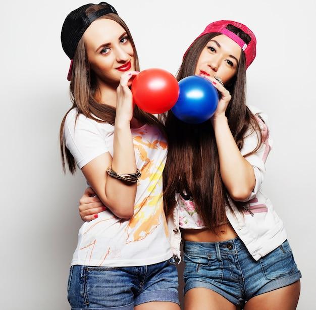 Dwie szczęśliwe hipsterki uśmiechają się i trzymają kolorowe balony na białym tle