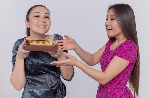 Dwie szczęśliwe i podekscytowane azjatyckie kobiety trzymające pudełko cukierków czekoladowych z okazji międzynarodowego dnia kobiet uśmiechnięte wesoło stojąc nad białą ścianą
