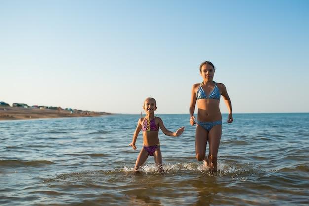 Dwie szczęśliwe i pozytywne siostry biegają wzdłuż morskich fal podczas wakacji w słoneczny, gorący letni dzień