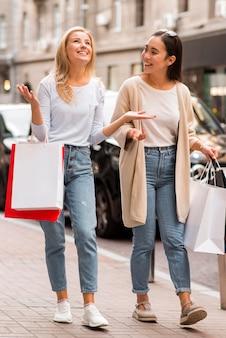 Dwie szczęśliwe kobiety chodzą po ulicy, trzymając torby na zakupy