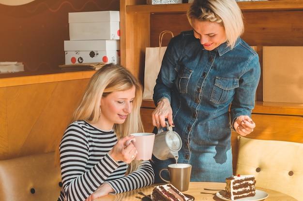 Dwie szczęśliwe kobiety siedzą w kawiarni, piją gorącą herbatę, opowiadają sobie śmieszne historie, są w dobrym nastroju, radośnie się śmieją. najlepsi przyjaciele