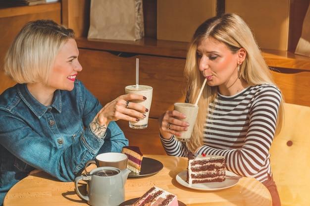 Dwie szczęśliwe kobiety siedzą w kawiarni, piją koktajl, opowiadają sobie śmieszne historie, są w dobrym nastroju, radośnie się śmieją. najlepsi przyjaciele