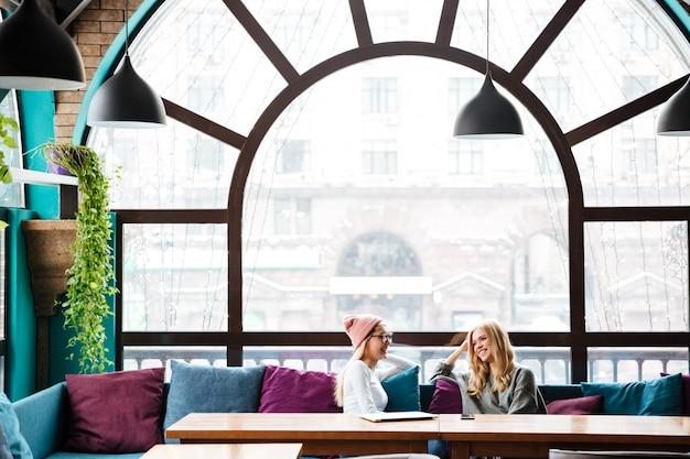 Dwie szczęśliwe kobiety siedzi i opowiada w kawiarni