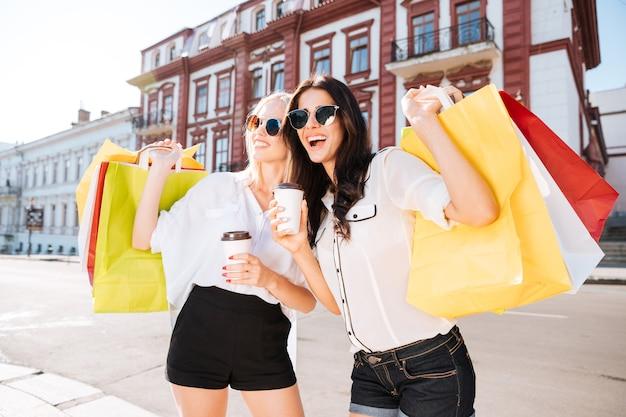 Dwie szczęśliwe kobiety trzymając torby na zakupy i zabawy, śmiejąc się na ulicy