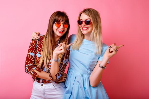 Dwie szczęśliwe ładne siostry najlepsi przyjaciele hipster kobiety bawiące się razem przy różowej ścianie, uściski i pocałunki, szczęśliwa para, modne jasne letnie ubrania i akcesoria, cele w związku.