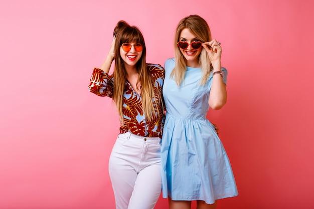 Dwie szczęśliwe ładne siostry najlepsze przyjaciółki hipster kobiety bawiące się razem na różowej ścianie, kolorowe modne letnie stroje, nastrój vintage.