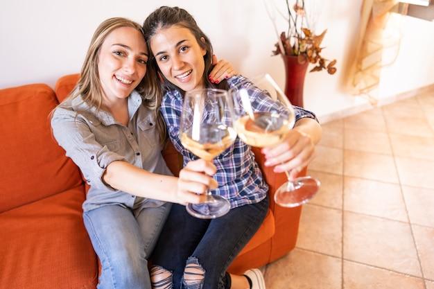 Dwie szczęśliwe lesbijki toastujące szampanem na kanapie, patrzące w kamerę, świętujące wolność wyboru i wspólne życie w nowej, nowoczesnej koncepcji rodziny przeciwko seksizmowi i różnicom społecznym
