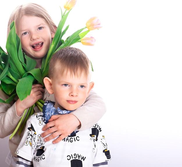 Dwie szczęśliwe małe dzieci - siostra i brat z kolorowymi kwiatami tulipanów uśmiechają się i przytulają na białej powierzchni