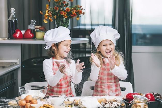 Dwie szczęśliwe małe dziewczynki gotują z mąki i ciasta przy stole w kuchni jest cudowne i piękne