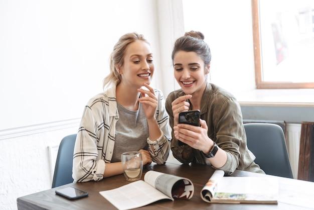 Dwie szczęśliwe młode kobiety przyjaciółki siedzące w kawiarni, pijące kawę, patrzące na telefon komórkowy