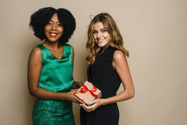 Dwie szczęśliwe młode kobiety różnych narodowości trzymają prezent na boże narodzenie i nowy rok na beżowym tle.