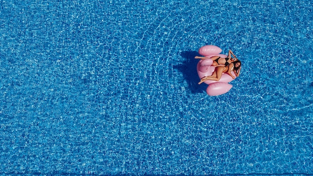 Dwie szczęśliwe młode kobiety z postaciami pływają w basenie dla flamingów. widok z góry.