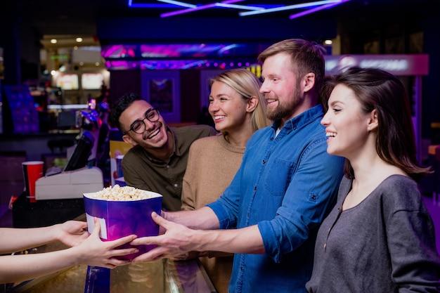 Dwie szczęśliwe młode pary kupują popcorn przy kasie w kinie podczas wspólnego oglądania filmu