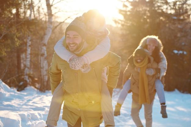 Dwie szczęśliwe młode pary w odzieży zimowej bawią się w słoneczny dzień