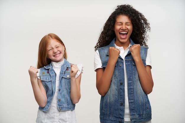 Dwie szczęśliwe młode urocze dziewczyny w zwykłych ubraniach zaciskające radośnie pięści i trzymające zamknięte oczy, będąc w duchu i szeroko uśmiechając się, stojąc na białym tle