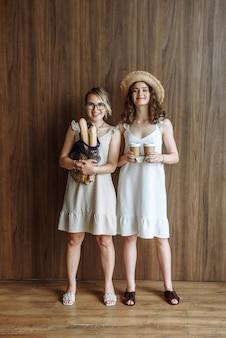 Dwie szczęśliwe modelki pozują w studio w sukienkach w nowym katalogu ubrań