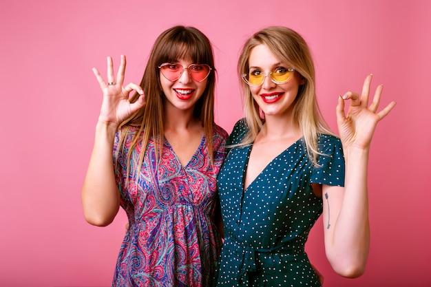 Dwie szczęśliwe najlepsze przyjaciółki siostry dziewczyny w modnych wiosennych letnich wydrukowanych jasnych sukienkach vintage i okularach przeciwsłonecznych, przytula i robi ok naukowy gest rękami.