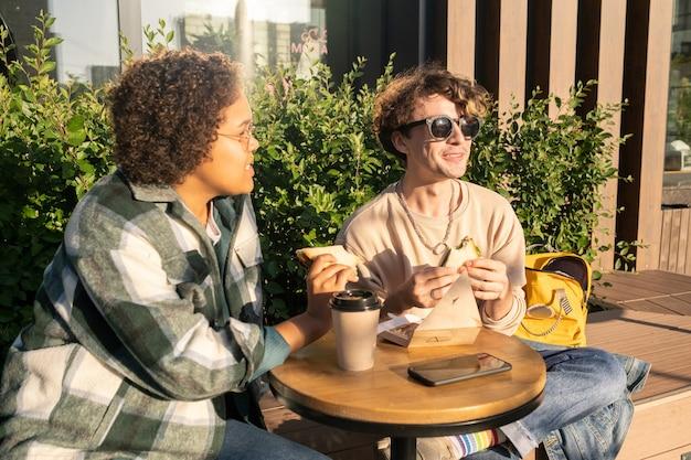 Dwie szczęśliwe nastolatki jedzą przekąskę i piją kawę na zewnątrz