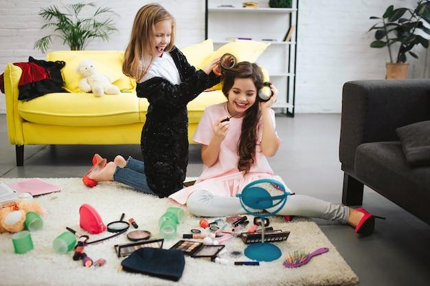 Dwie szczęśliwe nastolatki zabawy w pokoju. siedzą i stoją na dywanie. blondynka kręca włosy swojego przyjaciela. brunetka robi makijaż i patrzy w lustro. ona się uśmiecha.