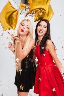 Dwie szczęśliwe, piękne młode kobiety z balonami w kształcie gwiazdy i konfetti bawią się na białym tle