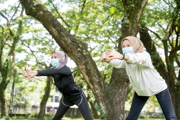 Dwie szczęśliwe przyjaciółki muzułmańskie kobiety ćwiczenia razem i nosić maskę
