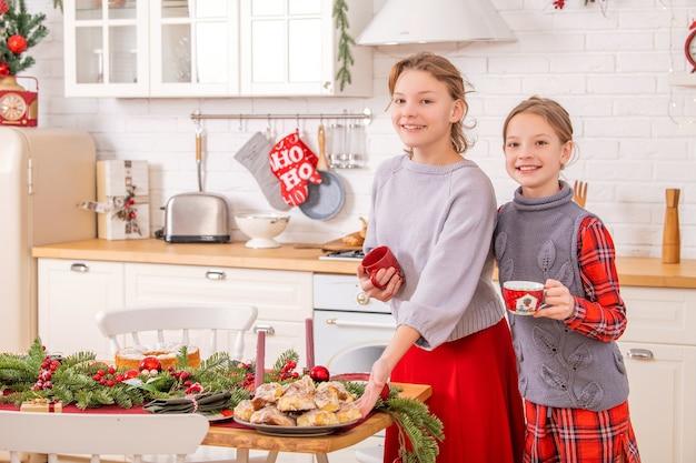 Dwie szczęśliwe siostry dekorują świąteczny stół w kuchni, trzymając w rękach kubki i słodkie ciasta.