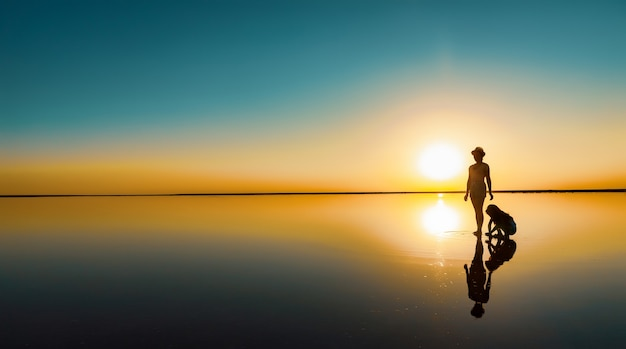 Dwie szczęśliwe, urocze siostry spacerują wzdłuż lustrzanego słonego jeziora, ciesząc się wieczornym ognistym zachodem słońca