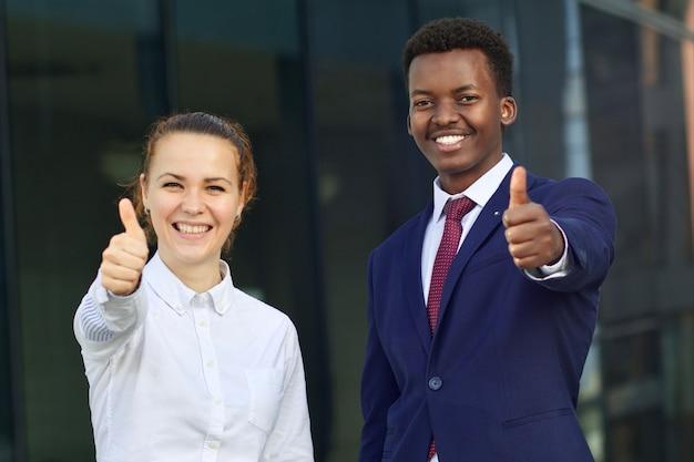 Dwie szczęśliwe uśmiechnięte osoby: biznesmen i bizneswoman. biała europejska młoda kobieta i czarny african afro american mężczyzna w formalnym garniturze na zewnątrz pokazując kciuk do góry, jak gest