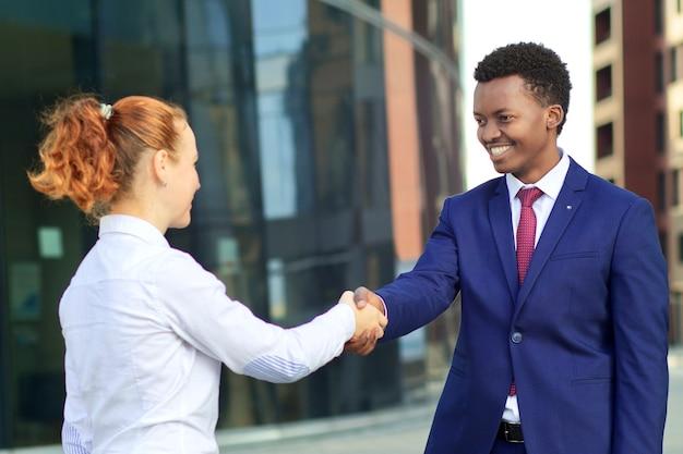 Dwie szczęśliwe uśmiechnięte osoby: biznesmen i bizneswoman ściskają ręce, witają. biała europejska młoda kobieta i czarny afroamerykanin mężczyzna w formalnym garniturze na zewnątrz