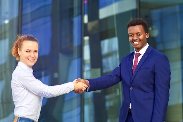 Dwie szczęśliwe uśmiechnięte osoby: biznesmen i bizneswoman ściskają ręce, witają.
