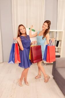 Dwie szczęśliwe wesołe dziewczyny demonstrujące swoje zakupy