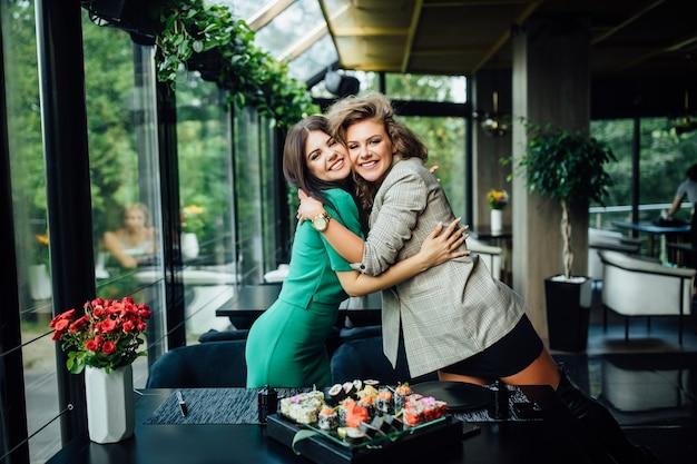 Dwie szczęśliwe wesołe przyjaciółki lub partnerzy biznesowi bawią się podczas lunchu w restauracji z owocami morza