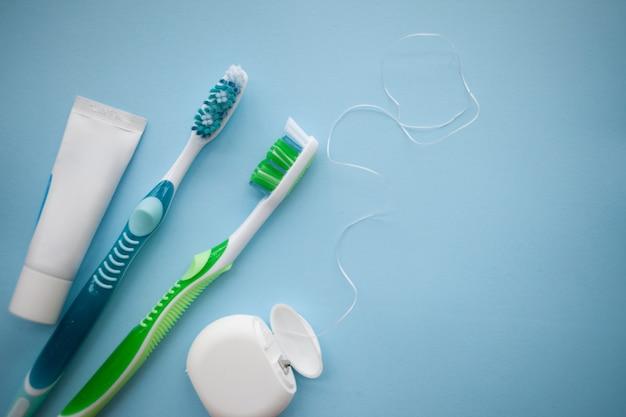Dwie szczoteczki do zębów i nić dentystyczna na niebiesko