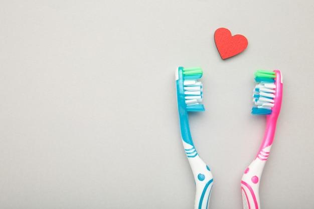 Dwie szczoteczki do zębów z sercem na białym tle