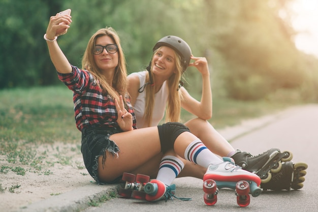 Dwie szczupłe i seksowne młode kobiety i wrotki. jedna kobieta ma łyżworolki, a druga ma łyżworolki. dziewczyny jeżdżą w promieniach słońca.