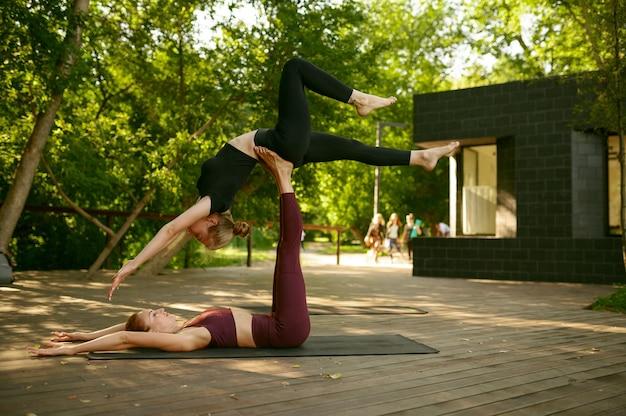Dwie szczupłe kobiety, wspólne ćwiczenia na grupowym treningu jogi w słoneczny dzień w parku