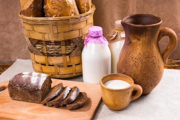 Dwie szklane butelki mleka między koszykiem chleba a drewnianym dzbankiem i filiżanką obok deski do krojenia pokrojonego w plasterki pumpernikla