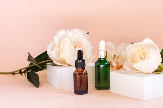 Dwie szklane butelki z naturalnymi olejkami eterycznymi na białym podium z kwiatem piwonii. produkt kosmetyczny na białym geometrycznym podium. naturalne organiczne produkty do samoopieki.