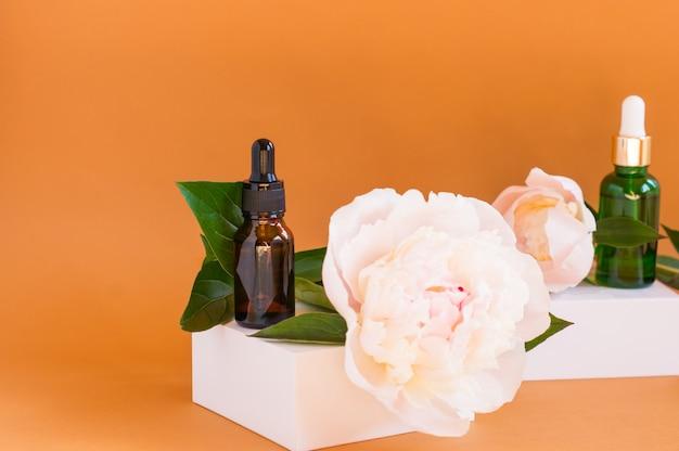 Dwie szklane butelki z zakraplaczem do użytku medycznego i kosmetycznego oraz białe delikatne kwiaty piwonii na beżowym tle. pielęgnacja skóry i koncepcja spa.
